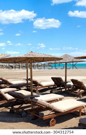 Beach chairs and sunshades on Mediterranean beach - stock photo