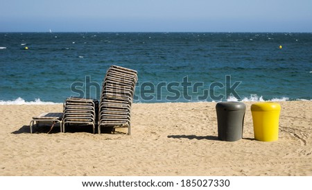 Beach chairs and trash bins on the beach - stock photo