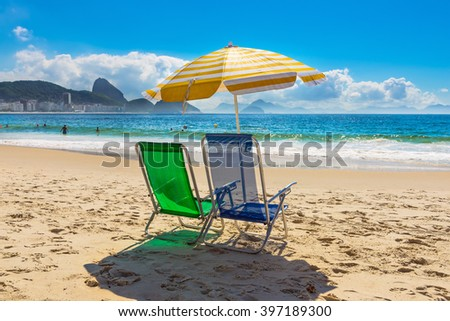 Beach chairs and umbrella on Copacabana beach in Rio de Janeiro, Brazil - stock photo
