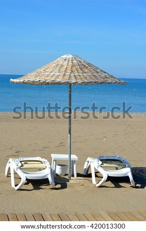 Beach chairs and umbrella on sandy beach  - stock photo