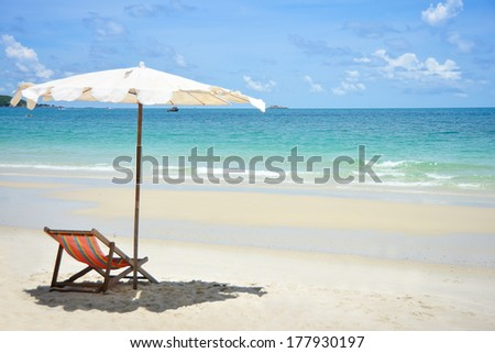 Beach chairs and umbrella on stunning tropical beach