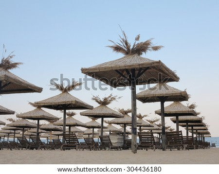 Beach chairs and umbrella on the sand near sea, blue sky and horizon - stock photo