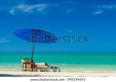 Beach chairs and umbrella on the white sand beach