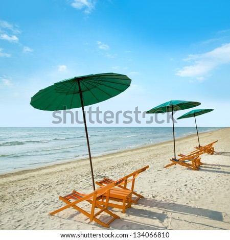 Beach chairs and umbrella on tropical sand beach.