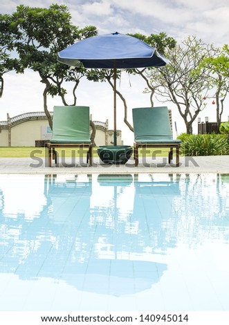 Beach chairs and umbrella side swimming pool