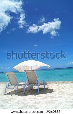 Beach Chairs and Umbrella with Ocean View - stock photo