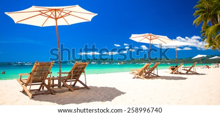 Beach chairs and umbrellas on exotic tropical white sandy beach - stock photo