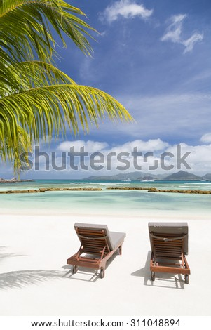 Beach chairs at perfect white beach in La Digue, Seychelles with a scenic coconut palm tree in the foreground