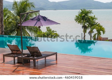 Beach chairs by the swimming pool with beautiful sea view