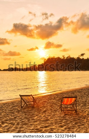 Beach chairs in the sand overlooking sea sunset. Thailand
