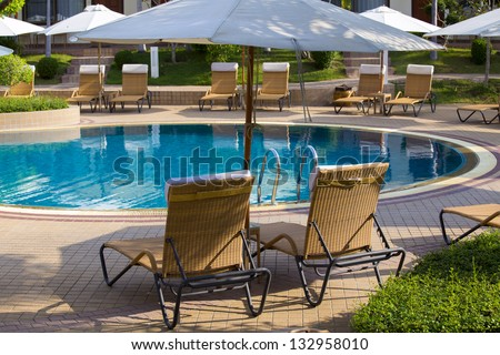 Beach chairs near swimming pool in tropical resort , Thailand. - stock photo