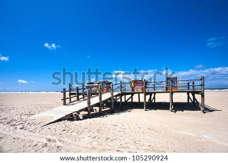 beach chairs on a pedestal made ??of wood, at the beach of Sankt Peter Ording, North Sea - stock photo