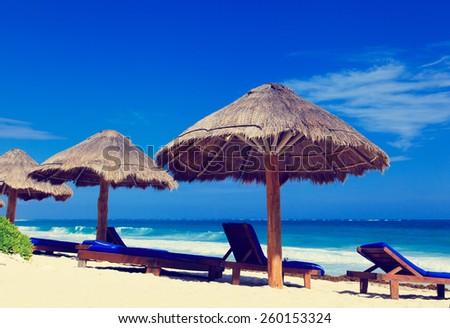 Beach chairs on exotic tropical white sand beach - stock photo