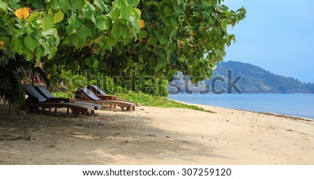 Beach chairs on idyllic tropical sand beach. - stock photo