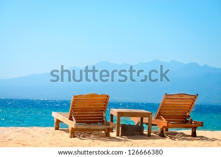 Beach chairs on perfect tropical yellow sand beach with blue sea and island on background, Gili, Bali, Indonesia - stock photo