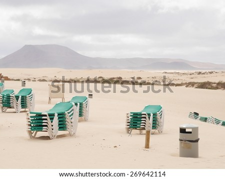 Beach chairs on the beach of Parque Natural de las Dunas de Corralejo. This park is a nature area with sand dunes in the north of the Canary island Fuerteventura belonging to Spain. - stock photo