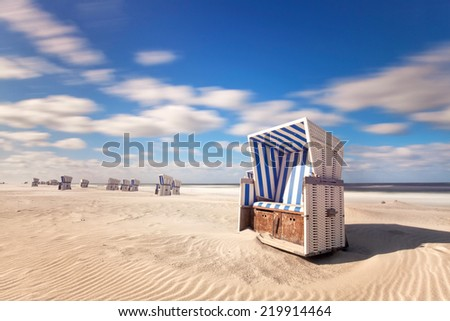 Beach - chairs on the island Sylt on stormy summer day. Germany North sea, long time exposure shot - stock photo