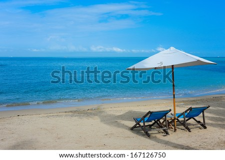 Beach chairs on the sand and blue skys - stock photo