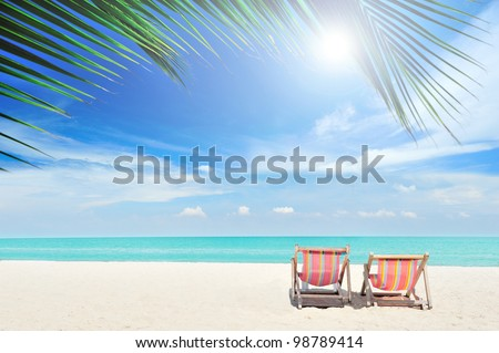 Beach chairs on the white sand beach, foreground with palm leaf, focus at chairs, with cloudy sky and sun - stock photo