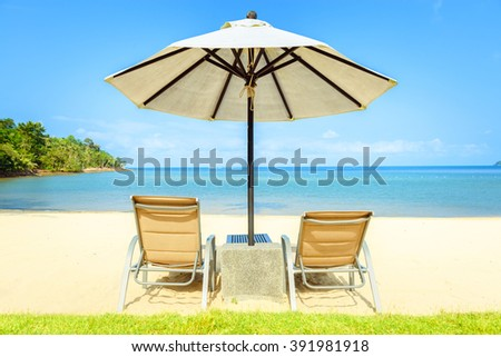 Beach chairs on the white sand beach with blue sky - stock photo
