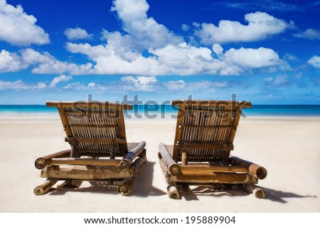 Beach chairs on the white sand beach with blue sky and palm trees