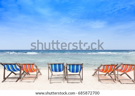 Beach chairs on the white sand beach with cloudy blue sky.