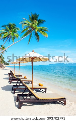 Beach chairs on the white sand beach with cloudy blue sky and su
