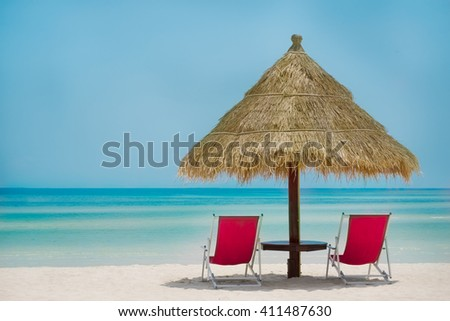 Beach chairs on the white sand beach with cloudy blue sky and sun - stock photo