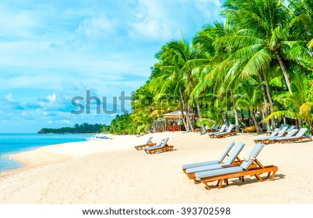 Beach chairs on the white sand beach with cloudy blue sky and sun. Vacation concept
