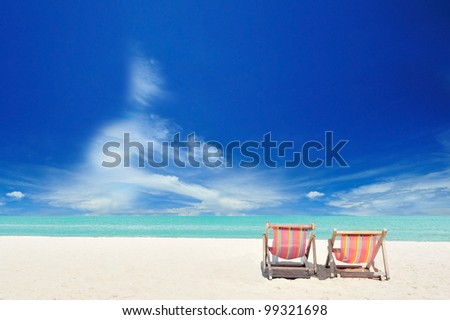 Beach chairs on white sand beach with cloudy blue sky and sun