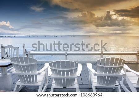 beach chairs overlooking tranquil ocean at sunset on old cape cod - stock photo