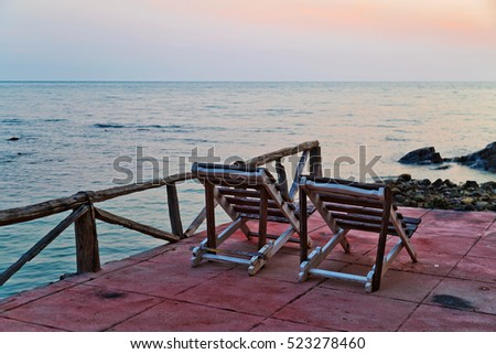 Beach chairs set at old pier overlooking sea sunset. Thailand