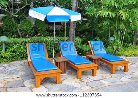Beach chairs side swimming pool - stock photo