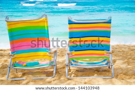 Beach chairs under by the ocean with sunscreen.