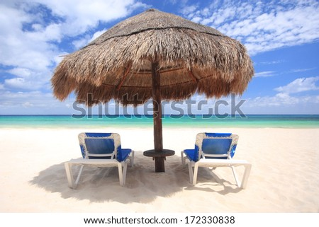 Beach chairs under thatched umbrella overlooking a tropical beach, Cozumel Mexico. - stock photo
