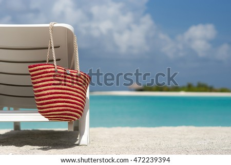 Beach chairs with bag on white sandy beach