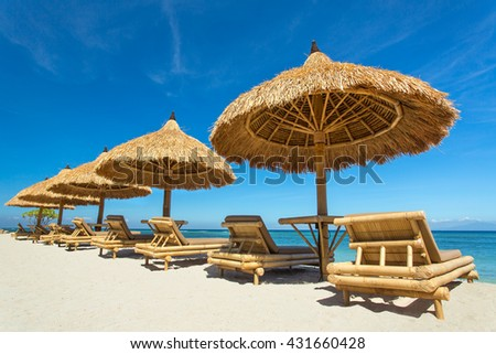Beach chairs with straw umbrellas on a beautiful tropical beach   - stock photo