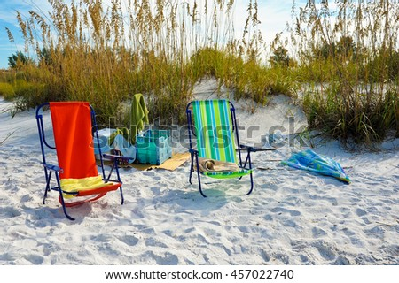 Beach Chairs with Towels and Umbrella for a day on the Beach - stock photo