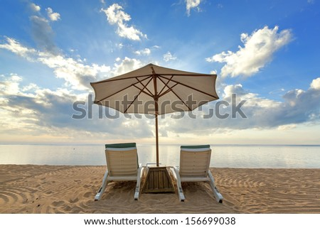 Beach chairs with umbrella and beautiful beach on a sunny day in Bali - stock photo