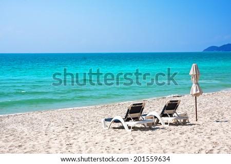 Beach chairs with umbrella and beautiful sand beach - stock photo