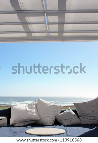 Beach club couch with ocean in the background - stock photo