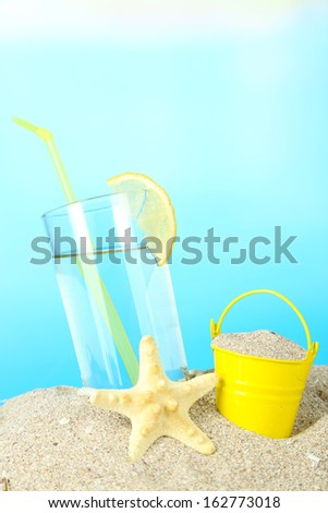 Beach cocktail in sand on blue background - stock photo