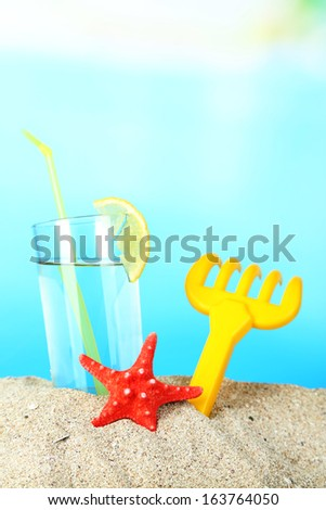 Beach cocktail in sand on blue background