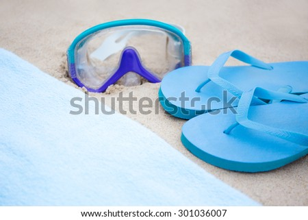 beach concept - flip flops, towel and diving mask on the sand