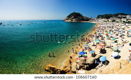 Beach Costa Brava with holiday-makers under the umbrellas and bathing people