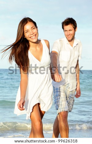 Beach couple happy holding hands. Young beautiful couple in love walking on beach at sunset. Asian woman, Caucasian man. - stock photo