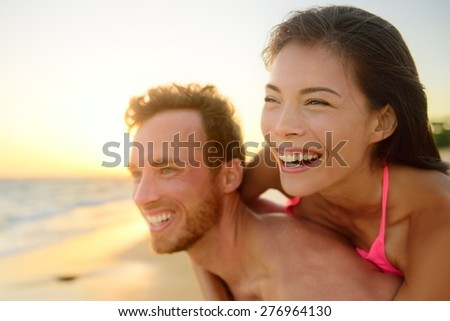 Beach couple laughing in love having fun romance on travel honeymoon vacation summer holidays. Young happy people, Asian woman and Caucasian man embracing outdoors on tropical beach in casual wear. - stock photo