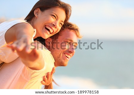 Beach couple laughing in love romance on travel honeymoon vacation summer holidays romance. Young happy people, Asian woman and Caucasian man embracing outdoors on tropical beach in casual wear. - stock photo