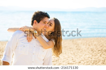 Beach couple laughing in love romance on travel honeymoon vacation summer holidays romance. Young happy people, hispanic man and Caucasian woman embracing outdoors on tropical beach in casual wear - stock photo