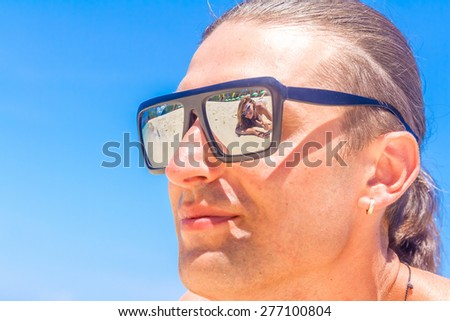 Beach couple looking. Happy young couple lying on sand under sunny summer sun. Travel holidays concept - stock photo